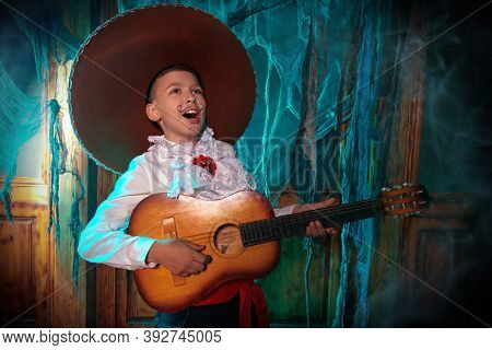 Boy in sombrero sings to the guitar an old wooden house. Dia de los muertos. Day of The Dead. Halloween.