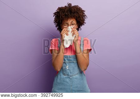 Portrait Of Sick African American Woman Sneezes In White Tissue, Suffers From Rhinitis And Running N