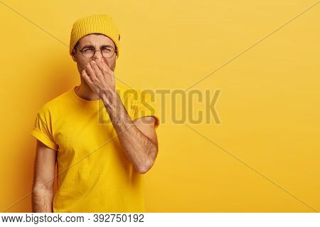 Disgusted Young Hipster Pinches Nose With Fingers, Looks In Disgust As Smells Something Stink, Wears