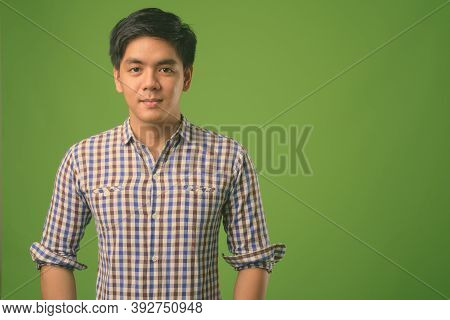 Young Handsome Filipino Man Against Green Background