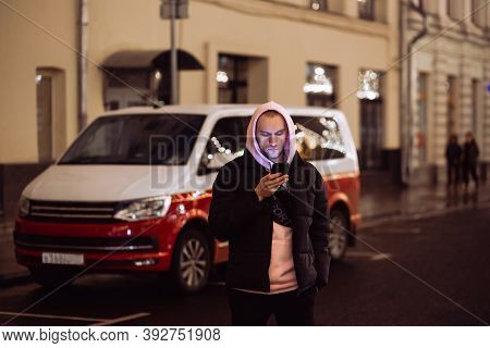 Man In Hood Looking Into His Smartphone In Background Of Car On Night Street