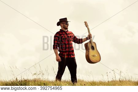 Country Music Concept. Guitarist Country Singer Stand In Field Sky Background. Country Style. Summer