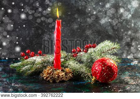 Christmas Decoration With A Burning Candle,  Snowy Fir Branches And Red Balls On A Dark Background.