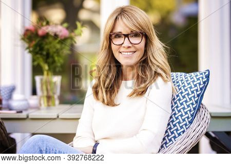Portrait Of Middle Aged Woman With Cheerful Smile Relaxing At The Armchair In The Balcony At Home.