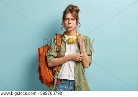 Dejected Young Woman In Low Spirit, Purses Lower Lip, Listens Audio Playlist With Headphones And Mob