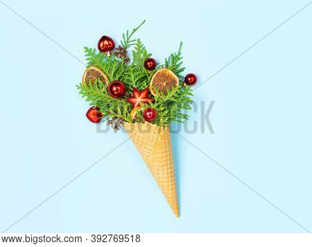 Waffle Cone With Thuja Sprigs And Christmas Toys On A Blue Background. New Year. Christmas Card. Cop