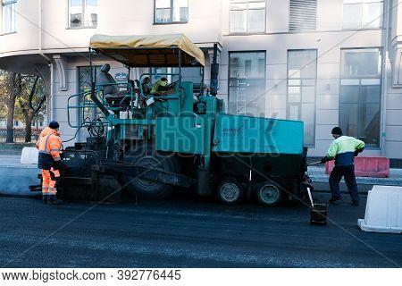 St.petersbug, Russia, 11.02.2020: Road Workers Are Repairing The Road. Asphalt Paver Making Asphalt.