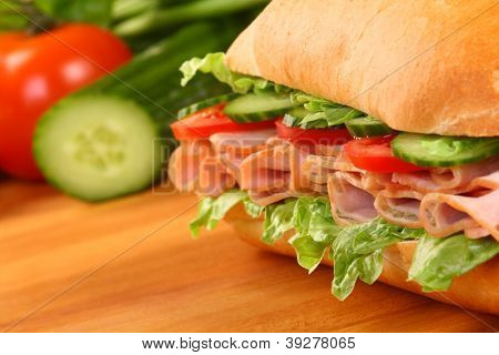 Fresh ham sandwich on wooden board - close up