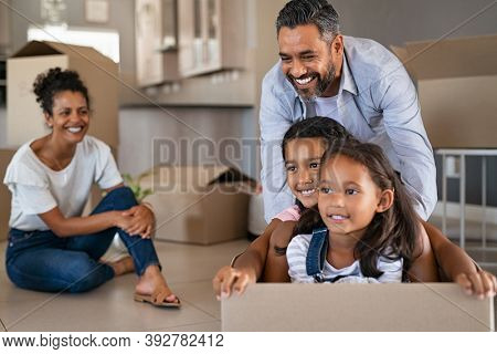 Happy children enjoying cardboard ride with indian father in new home. Cheerful daughters sitting in carton box while dad pushing them. Smiling parents with children having fun during moving day.