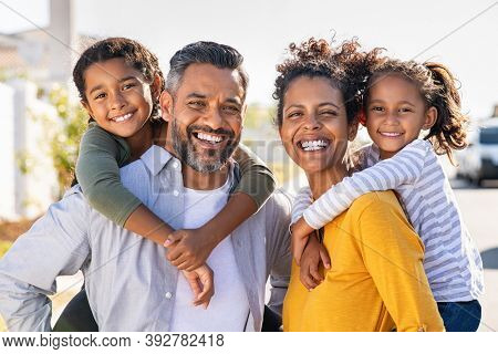 Mixed race parents giving piggyback ride to their children. Portrait of happy african mother and indian father with daughters looking at camera. Smiling family standing with their little girls.