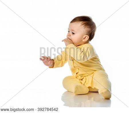 Little Baby Child In Yellow Jumpsuit With Hand In Mouth Scratching First Teeth. Teething, Oral Care