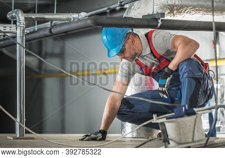 Caucasian Hvac Worker In His 40s Wearing Professional Safety Harness Working Inside Warehouse Buildi