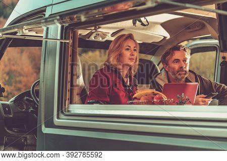 Caucasian Couple Watching Exciting Tv Game Inside Self Made Camper Van Rv During Scenic Autumn Weeke
