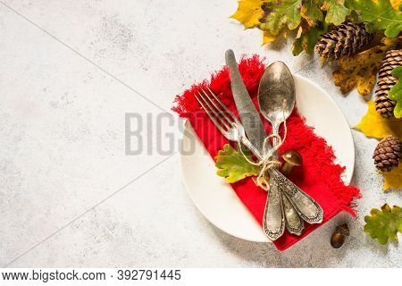 Thanksgiving Food Concept. Autumn Table Setting With White Plate, Silverware And Fall Decorations At