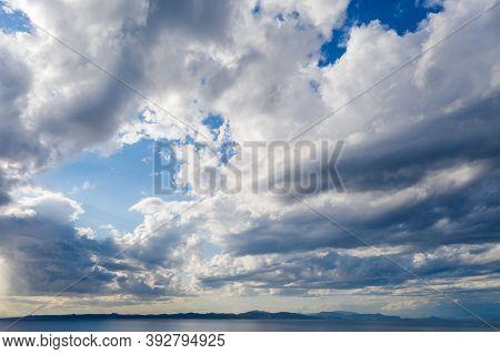 Kea, Tzia Island, Destination Greece. Silver Sunbeams On The Sea Through Clouds Background.