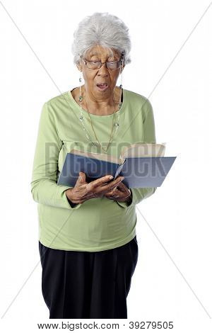 An attractive, ninety-year-old African American woman singing praise from a hymnal.  On a white background.