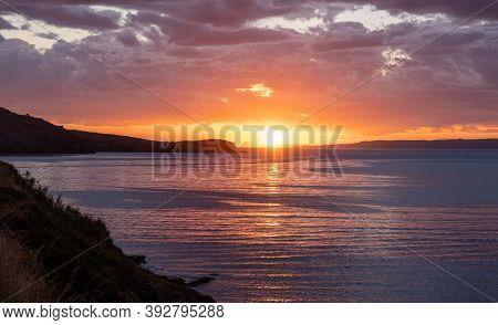 Kea, Tzia Island, Destination Greece. Sunset, Sunrise Orange Through Clouds Background