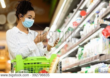 Grocery Shopping. African American Woman In Mask Using Smartphone Choosing Milk Buying Food Grocerie