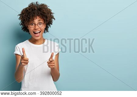 Joyous Dark Skinned Woman Points Both Fore Fingers Straightly At Camera, Wears Casual Clothing, Happ