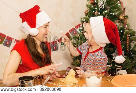 Happy Mother And Child At Home Making Dough. Family Idyll, Little Helper. Baking Christmas Cookies.