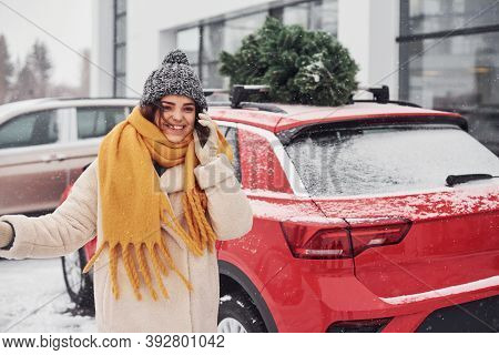 Positive Young Girl Standing Near Car With Green Christmas Tree On Top.