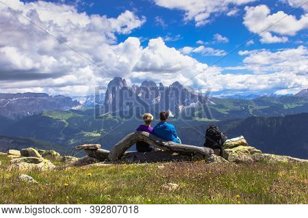 Active Sporty Couple Having A Rest On The Peak Of Dolomites, Italy.succsseful Backpackers Enjoying V