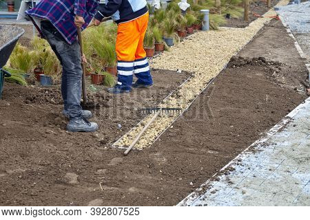 Workers Installing Flower Beds With Black Earth And Decorative Stones. Concept Of Beautification Of