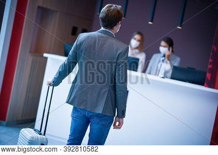 Businessman in mask at the reception of a hotel checking in