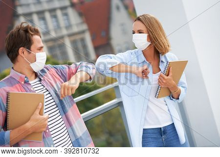 Couple of students wearing masks while saying hi in the campus