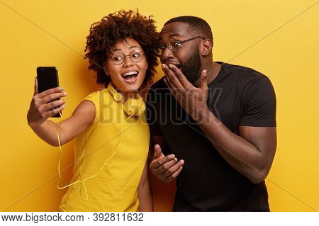 Joyous Dark Skinned Female And Male Couple Have Fun Together, Pose For Making Selfie Portrait, Smile