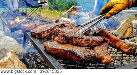 Steaks On The Grill With Yellow Gloves And Tong Camping Grilling Barbeque, Bbq Meat Grilled.