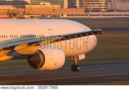 Close Up Of Wide-body Passenger Aircraft With Wing And Engine Taxing On The Runway During Sunset. Ai