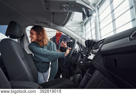 Professional Salesman Assisting Young Girl By Choosing New Modern Automobile Indoors. Woman Sitting