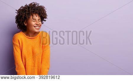 Optimistic Happy Dark Skinned Woman Closes Eyes, Feels Enthusiastic, Grins Gladfully, Keeps Eyes Clo