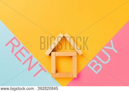 Rent Buy. A House Made Of Wooden Cubes With Rent And Buy Inscriptions On Colorful Backgrounds