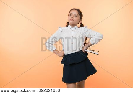Girl Cute Schoolgirl In Uniform Hold Book Or Textbook Yellow Background. Diligent Pupil Get Knowledg