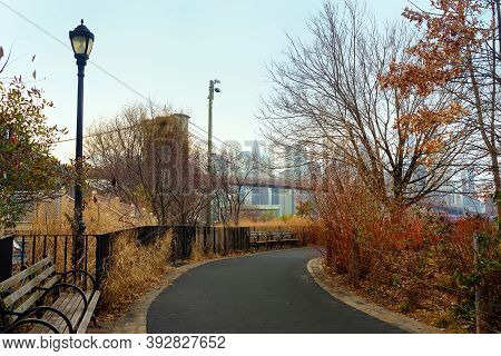Alley Of Main Street Park On The Background Of Famous Brooklyn Bridge In New York In Winter Day. Par