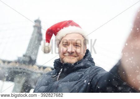 Local Man In A Santa Claus Hat Takes Selfie On Street Near The Manhattan Bridge In New York City On
