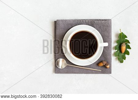 A Cup Of Black Coffee On A Gray Napkin With A Teaspoon, Acorns And Oak Leaves. Acorn Coffee Without