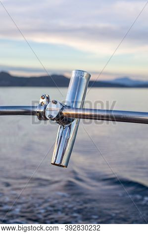 A Stainless Steel Fishing Rod Holder Mounted On The Rail Of A Sailboat Or Motorboat To Keep Equipmen