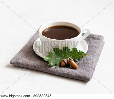 Black Coffee On A Gray Napkin, Acorns And Oak Leaf On A White Background. Acorn Coffee Without Caffe