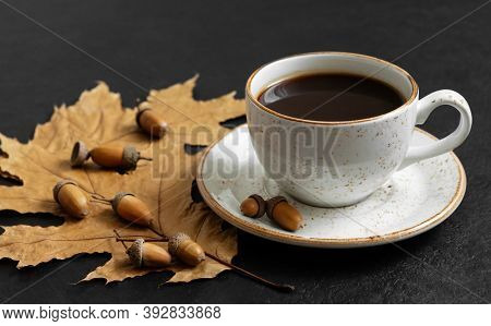Autumn Still Life With A Cup Of Coffee, Leaves And Acorns On A Black Background. Acorn Coffee. Caffe