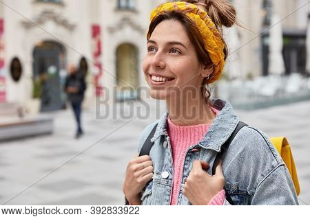 Carefree European Woman With Toothy Smile, Wears Yellow Headband And Denim Jacket, Enjoys Nice Day,