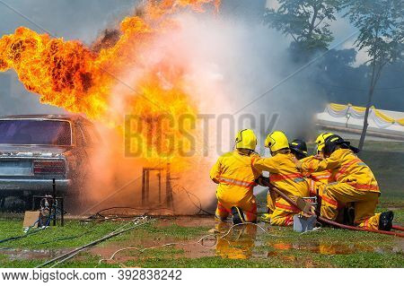 Fireman Using Water And Extinguisher Car Is On Fire,firefighter Using Extinguisher And Water From Ho