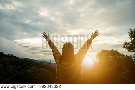 Freedom Concept. Happy Woman On The Sunset In Nature In Winter With Arm Raised And Open Hand