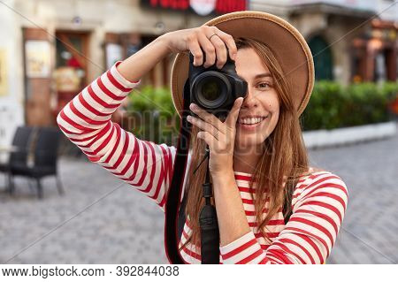 Professional Photographer Makes Amateur Photos While Strolls In City During Excursion, Smiles Positi