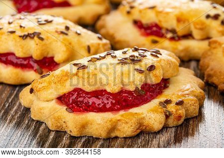 Close Up Of Few Shortbread Cookies With Raspberry Jam And Linseeds On Dark Wooden Table