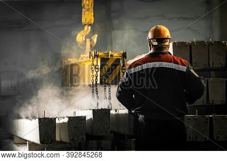 A Male Worker Controls The Production Process In A Factory As A Crane Moves A Reinforced Concrete Pr