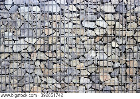 Fence Of House Is Made Of Gabion Filled With Rock Stones