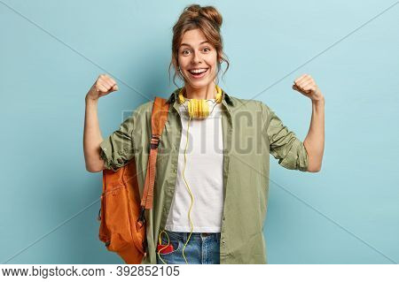 Strong Powerful Woman Raises Hands And Shows Muscles, Has Glad Expression, Wears Headphones, Has Ruc